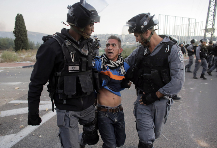 Israeli policemen detain an Arab youth during clashes at the entrance to the town of Kfar Kanna, in northern Israel. Thousands took to the streets on Saturday hours after Khayr al-Din al-Hamdan was shot by police, after he attacked them as they came to arrest a relative. (Ammar Awad/Reuters)