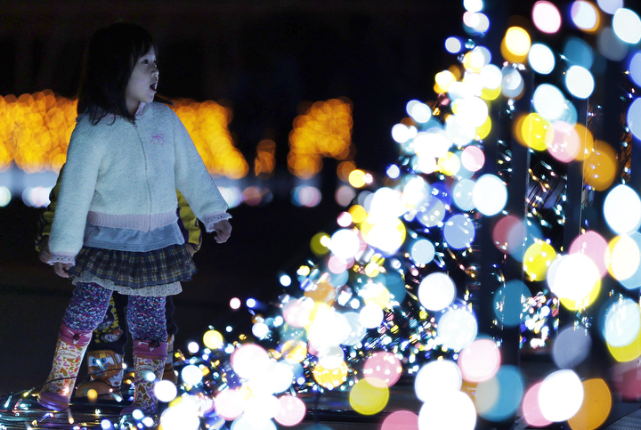 A girl looks at a Christmas illumination at Yomiuri Land amusement park in Tokyo. The amusement park uses three millions LED lights for its Christmas illumination. (Yuya Shino/Reuters)