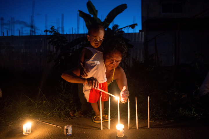 A woman and her child light a candle on the roadside in San Jose during the candlelight memorial in Tacloban, Leyte, Philippines. People lined the roads with candles all across Tacloban from the airport to downtown in remembrance of the victims of Typhoon Haiyan. Residents and typhoon survivors from across the central Philippines attended memorial services, candlelight vigils and visited mass graves honouring those who lost their lives one year ago when Typhoon Haiyan, the strongest typhoon ever to make landfall swept across the region, leaving more than 6000 dead and many more homeless.Chris McGrath/Getty Images)