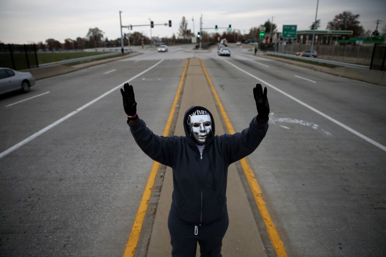 """Demonstrators yell """"Hands Up, Don't Shoot"""" alongside a highway overpass to voice their opinions as the area awaits a grand jury decision on November 15, 2014 near Ferguson, Missouri. The area around St Louis, Missouri prepares for the grand jury decision in the shooting death of Michael Brown by Darren Wilson, a Ferguson police officer. (Photo by Joe Raedle/Getty Images)"""