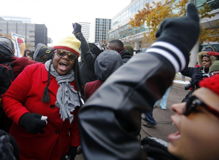 Demonstrators take part in a protest in front of the building where the grand jury is looking into the shooting death of Michael Brown in Clayton, Missouri, November 17, 2014. Several dozen demonstrators took to the streets Monday in Clayton, Missouri, where a grand jury is determining whether to file criminal charges against a white police officer who shot and killed an unarmed black teen in August. Protesters expressed anger that, 101 days after 18-year-old Brown was shot and killed in Ferguson, Missouri, it was still unclear what will happen to the officer, Wilson. (Jim Young/Reuters)