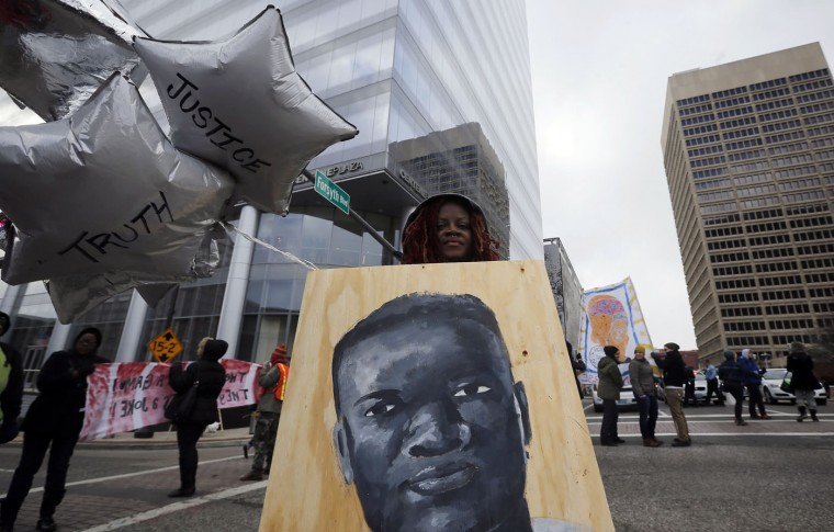 A demonstrator blocks an street intersection during a protest over the shooting death of Michael Brown in Clayton, Missouri, November 17, 2014. Several dozen demonstrators took to the streets Monday in Clayton, Missouri, where a grand jury is determining whether to file criminal charges against a white police officer who shot and killed an unarmed black teen in August. Protesters expressed anger that, 101 days after 18-year-old Brown was shot and killed in Ferguson, Missouri, it was still unclear what will happen to the officer, Wilson. (Jim Young/Reuters)