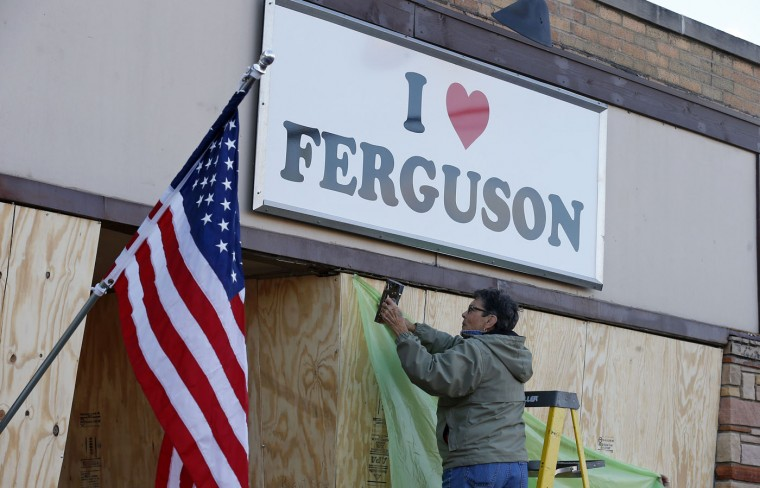 "Susan Akenbrand works on the boarding up of the ""I Love Ferguson"" store in preparation for the grand jury verdict in the shooting death of Michael Brown in Ferguson, Missouri, November 18, 2014. The grand jury is expected to reach a decision this month on whether to indict Darren Wilson, the white police officer who shot and killed the 18-year-old Brown, who was black, on Aug. 9 in the St. Louis suburb of Ferguson. (Jim Young/Reuters)"