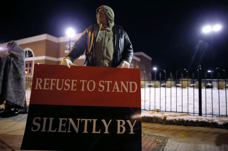 A demonstrator takes part in a protest over the shooting death of Michael Brown in front of the Ferguson Police Department in Ferguson, Missouri, November 17, 2014. Missouri's governor declared a state of emergency on Monday and authorized the state's National Guard to support police in case of violence after a grand jury decides whether to indict Darren Wilson, a white police officer who fatally shot Brown, an unarmed black teenager. (Jim Young/Reuters)