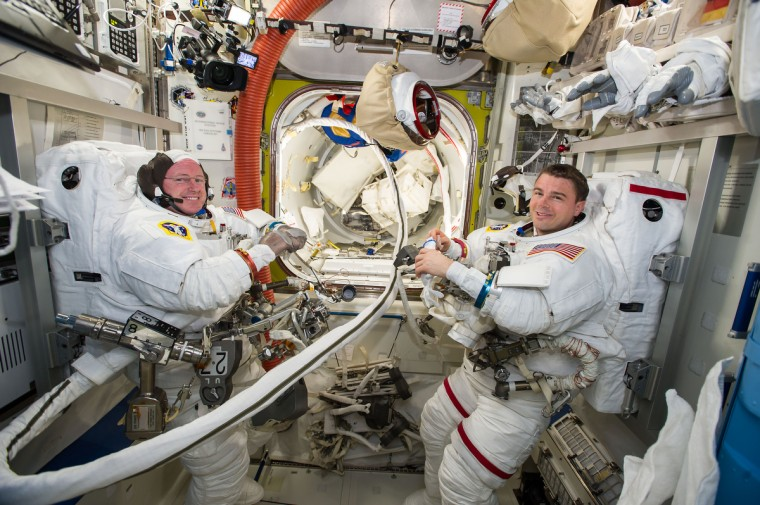 Flight Engineers Reid Wiseman (right) and Barry Wilmore spent most of Oct. 14 completing preparations for their 6 ½-hour Oct. 15 spacewalk. The two astronauts set up their spacesuits and tools in the equipment lock of the Quest airlock. (NASA photo)