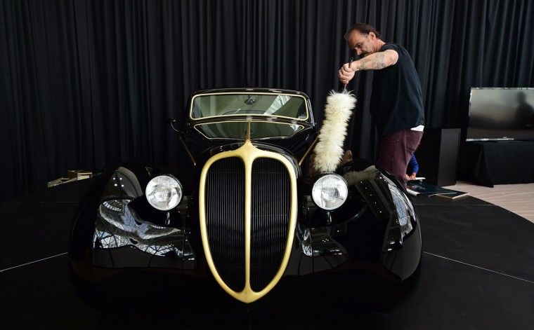 Rick Dore dusts 'The Black Pearl', a custom-built vehicle he designed and based off a 1948 Jaguar Frame, as he prepares his display on the opening press and trade day at the LA Auto Show in Los Angeles, California on November 18, 2014. Nearly 60 North American and World vehicle debuts will be unveiled at this years auto show which opens to the public from November 21 to 30. (Frederic J. Brown/AFP/Getty Images)
