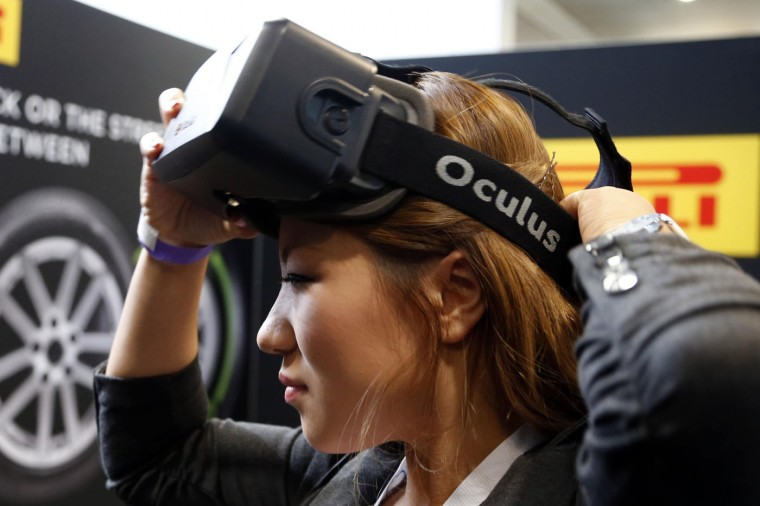 A woman puts on an Oculus virtual reality headset during preparations for the 2014 LA Auto Show in Los Angeles, California November 18, 2014. (Lucy Nicholson/Reuters)