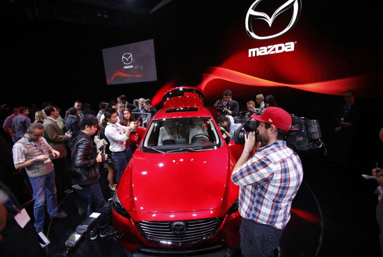 Members of the media look over the Mazda CX-3 Compact Crossover Utility vehicle during the model's world debut at the Los Angeles Auto Show in Los Angeles, California November 19, 2014. (Mario Anzuoni/Reuters)