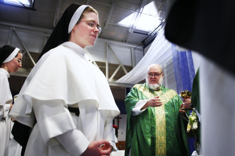 Reverend Michael Roach receives the gifts from the Dominican Sisters as Sister Anne Jochin, of Nashville, Tennessee, walks by. On Sunday August 28, Mount de Sales Academy marked the 20th anniversary of the Dominican Sisters at the school, which is a teaching order based in Tennessee. (Andrew Henderson/File photo)