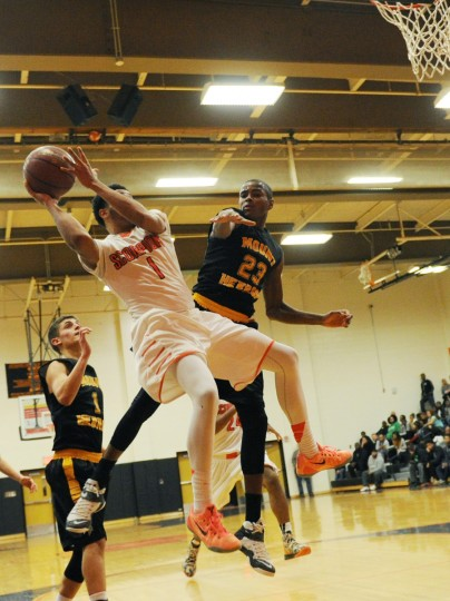 Oakland Mills' Daniel Kiely, center, and Mt. Hebron's Aaren Smith, right, rise together as Kiely takes a shot during a boys basketball game at Oakland Mills High School in Columbia, Monday, Dec. 8, 2014. (Jon Sham/BSMG)