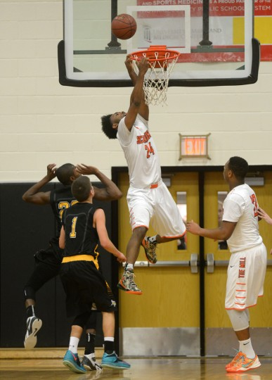 Oakland Mills' Will Robinson Jr. hangs on the rim after a failed dunk attempt during a boys basketball game at Oakland Mills High School in Columbia, Monday, Dec. 8, 2014. (Jon Sham/BSMG)