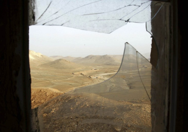 A window with broken glass overlooks the Lebanese-Syrian border as seen from a Lebanese military post, near the site of an ambush where gunmen killed at least six Lebanese soldiers, in the mountainous border town of Ras Baalbek December 3, 2014. Gunmen killed at least six Lebanese soldiers when they attacked an army patrol near the border with Syria on Tuesday, the army and a Lebanese security source said. The source said the gunmen crossed from Syria to the mountainous border town of Ras Baalbek after dark and ambushed the patrol. Clashes between gunmen and a special army unit erupted after the attack and the army was able to retrieve the bodies of six of its soldiers. Picture taken from the Lebanese side of the Lebanese-Syrian border. (Mohamed Azakir/Reuters photo)