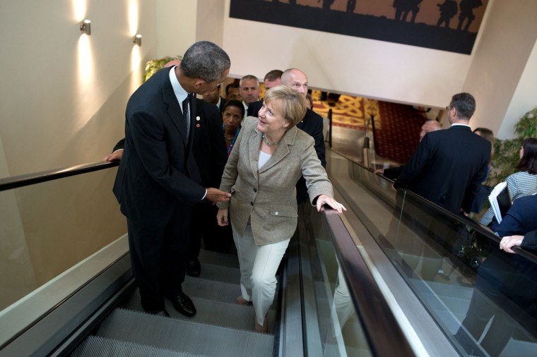 "Sept. 4, 2014 ""Meetings happen everywhere including on the escalator. Here, the President continues a conversation with German Chancellor Angela Merkel following their meeting with other leaders at the NATO Summit in Newport, Wales."" (Official White House Photo by Pete Souza)"