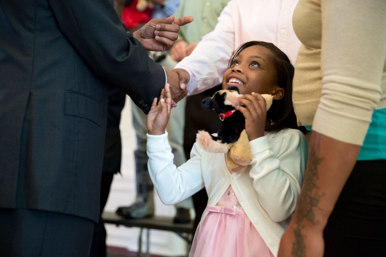 "Sept. 22, 2014 ""As the President was greeting wounded warriors and their families, I focused on this young girl as the President shook hands with her father. I love how she's touching the President's arm as she looks up at him almost in disbelief."" (Official White House Photo by Pete Souza)"