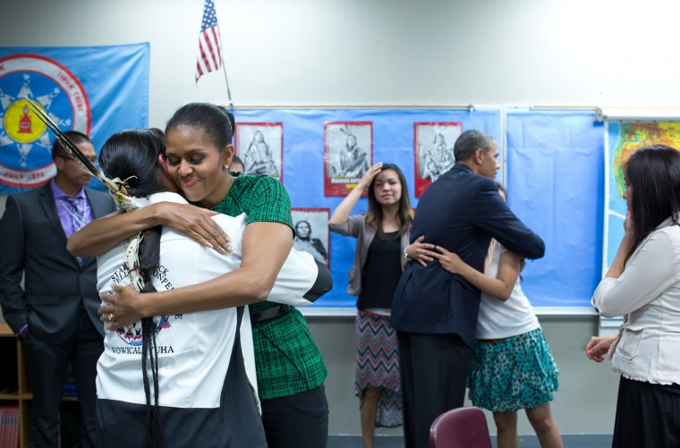 "June 13, 2014 ""The First Lady and the President hug Native American youth following a meeting with them at the Standing Rock Sioux Tribe Reservation in Cannon Ball, North Dakota. The Obama's were so moved by this meeting that they arranged for these youth members to visit them at the White House later in the year. A photograph from that visit also appears in this gallery."" (Official White House Photo by Pete Souza)"