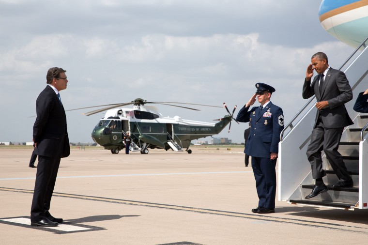 "July 9, 2014 ""The President salutes an Air Force member as he disembarks Air Force One to greet Texas Gov. Rick Perry upon arrival at Dallas/Fort Worth International Airport. The President and Gov. Perry later discussed immigration aboard Marine One en route to a meeting with other officials."" (Official White House Photo by Pete Souza)"