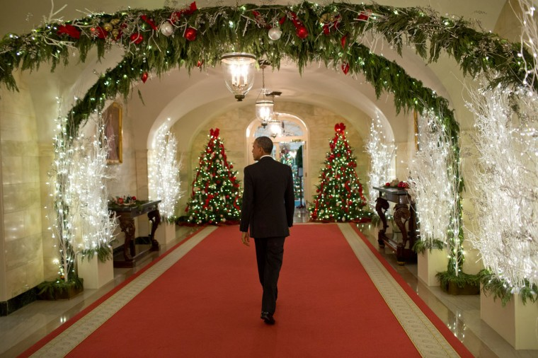 "Dec. 12, 2014 ""The President walks through the Ground Floor Corridor of the White House as he heads back to the Oval Office following a holiday reception."" (Official White House Photo by Pete Souza)"
