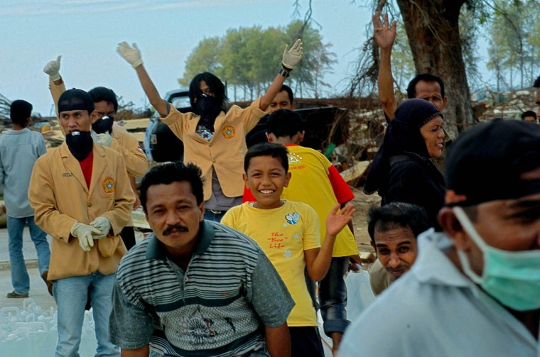Some Lhok Nga residents wave to the crew of the U.S. Navy helicopter that takes off after delivering water and rice while others duck to reduce getting hit with the air from the rotors Tuesday, Jan. 18, 2005 following a tsunami that swept through the town in December. (Karl Merton Ferron, Baltimore Sun)