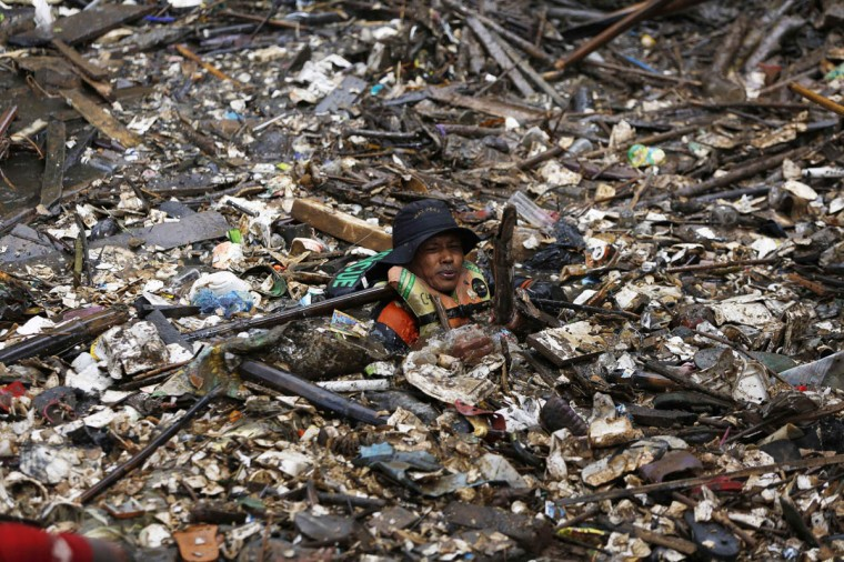 A volunteer clears rubbish from the Ciliwung River in the Jatinegara district of Jakarta, December 3, 2014. More than 1,000 soldiers and volunteers cleared 80 tons of rubbish after flooding hit parts of the capital last week, local media reported. (Beawiharta/Reuters photo)