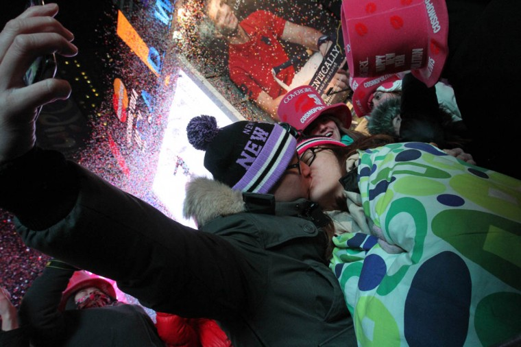 Bruce Li, left, and his girlfriend Phyllis Zhong, of Toronto, kiss just after midnight in New York's Times Square. (Tina Fineberg/AP photo)