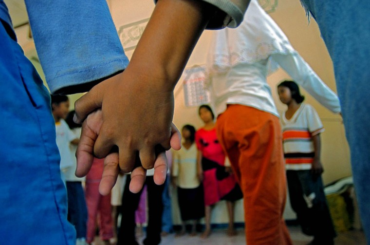Children hold hands as they begin a game at Camp MNS Desa Lamgugop Monday, Jan. 17 2005. Save The Children has begun sponsoring safe spaces for the children, who have been victimized by a tsunami that swept through the town in December. (Karl Merton Ferron, Baltimore Sun)