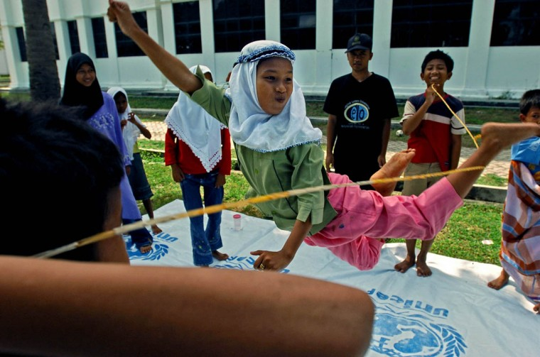 "Humaira, 11, to the delight of the other children, leaps while kicking her left foot out to catch the rubber band rope held by classmates in a game opposite of the ""limbo."" (Karl Merton Ferron, Baltimore Sun)"
