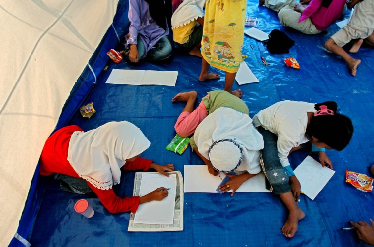 Humaira Puspitadewi, 11, center, sketches with her new friends Lia Azrina, 11, left, and Norul Husna, 9, during class in a tent at Darussalem. (Karl Merton Ferron, Baltimore Sun)