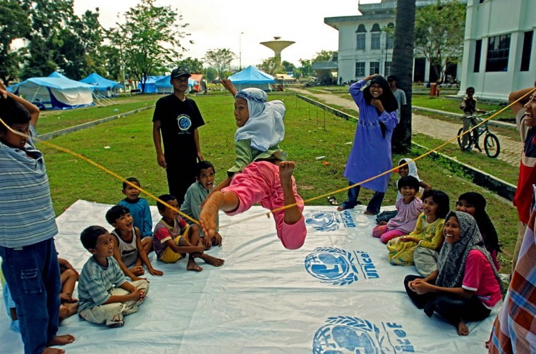 """Humaira, 11, to the delight of the other children leaps, kicking her left foot out to catch the rubber band rope (it's like a reverse form of """"limbo,"""" where the line is raised and the subject must go above the line) as they attempt to get back on their feet January 14, 2005 after a tsunami destroyed their home and disrupted their lives in December. (Karl Merton Ferron, Baltimore Sun)"""