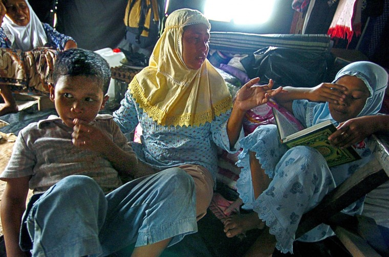 Humaira Puspitadewi, 11 rubs her eyes as she reads the Koran as her mother Badria M. Hasyim sees that she is sleepy while her surviving brother Ahmad Chumaini, 9 (left) looks on as they attempt to get back on their feet January 16, 2005 after a tsunami destroyed their home and disrupted their lives in December. Humaira lost a younger brother, Raja Iqbal, 4, plus an additional 58 extended family. (Karl Merton Ferron, Baltimore Sun)