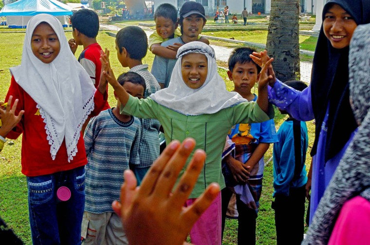 Humaira, 11 (center) claps hands with friends Lia Azrina, 11 (left) and Feni Ulfina, 14 while they stand in a circle, starting a chant in a children's game. (Karl Merton Ferron, Baltimore Sun)