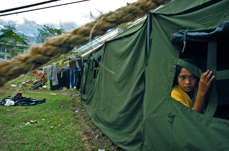 Humaira, 11, looks out the window of the military tent that her family now calls home while clothing from other families (background) hangs on the lines that support the tent as the families attempt to get back on their feet January 13, 2005 after a tsunami destroyed their home and disrupted their lives in December. (Karl Merton Ferron, Baltimore Sun)