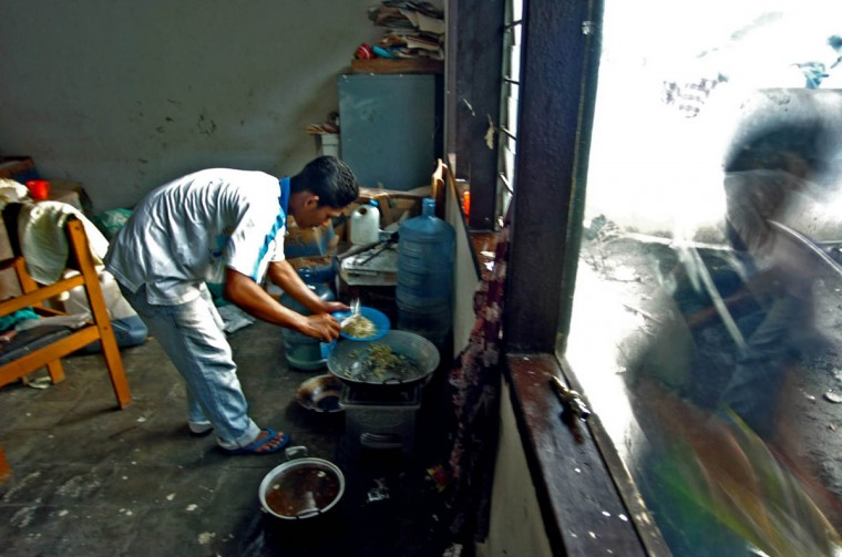 Muchlia stir- fries supper as another displaced resident walks past at Rukoh's shelter Friday, Jan. 14, 2004. Residents of Banda Aceh, which suffered one of the worst disasters in modern history after half of the town was wiped out by an earthquake and tsunami, struggle to get the area back on track. (Karl Merton Ferron, Baltimore Sun)