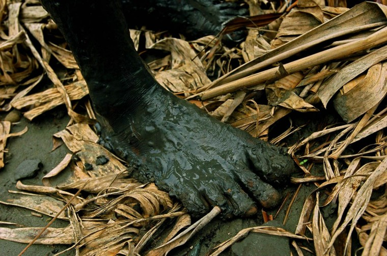 The feet of a Rukoh resident are caked with mud as he helps extract usable lumber Friday, Jan. 14, 2004 from the debris left by the Christmas tsunami that slammed into Rukoh. (Karl Merton Ferron, Baltimore Sun)