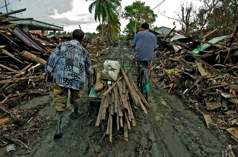 Retrieving different sizes and cuts of lumber, residents trudge between two mounds of debris left inland from structures destroyed by the Christmas tsunami in order to use them at village Rukoh Friday, Jan. 14, 2004. Residents of Banda Aceh, which suffered one of the worst disasters in modern history after half of the town was wiped out, struggle to right themselves in an area already financially struggling. (Karl Merton Ferron, Baltimore Sun)