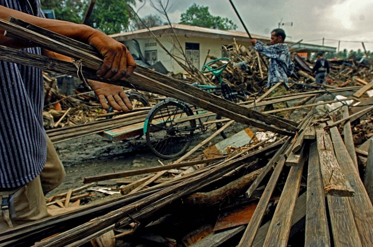 Residents pull and tug at lathes from piles of debris left inland from structures destroyed by the Christmas tsunami in order to use them at Rukoh village Friday, Jan. 14, 2004. (Karl Merton Ferron, Baltimore Sun)