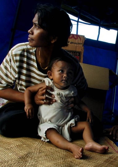 Peering from the tent she shares with her husband, Ernawaty and her baby Roaeja, one- year- old, still have no where else to live following the Christmas tsunami but the tent they sit inside on the grounds at Masjid Kopelma Darussalam. (Karl Merton Ferron, Baltimore Sun)