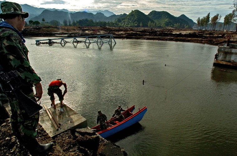 Indonesian Military Police start work to help rebuild the washed out Lhok Nga River bridge Wednesday, Jan. 19, 2005 following a tsunami that swept through the town in December. (Karl Merton Ferron, Baltimore Sun)