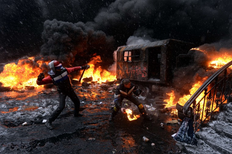 A protestor throws a molotov cocktail at riot police in the centre of Kiev on January 22, 2014. Ukrainian police today stormed protesters' barricades in Kiev as violent clashes erupted and activists said that one person had been shot dead by the security forces. Total of two activists shot dead during clashing. The move by police increased tensions to a new peak after two months of protests over President Viktor Yanukovych's failure to sign a deal for closer ties with the EU. Vasily Maximov/AFP/Getty Images