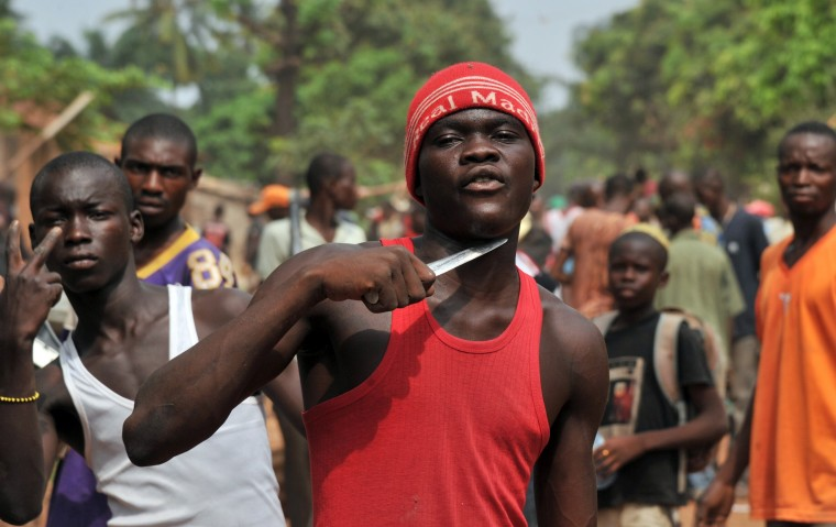 A man holds a knife to his throat claiming that he is looking for Muslims to cut off their heads in the 5th district of Bangui on February 9, 2014. According to witnesses, at least ten people have been killed since the night before in central Bangui, and many buildings burned, after violence broke out near the district hall of Bangui's 5th district. Large-scale looting was also taking place in the same neighbourhood in the morning of February 9 despite the deployment of French troops and Central African gendarmes. The International Criminal Court in the Hague said on February 7 it had opened an initial probe into war crimes in the Central African Republic. Issouf Sanogo/AFP/Getty Images