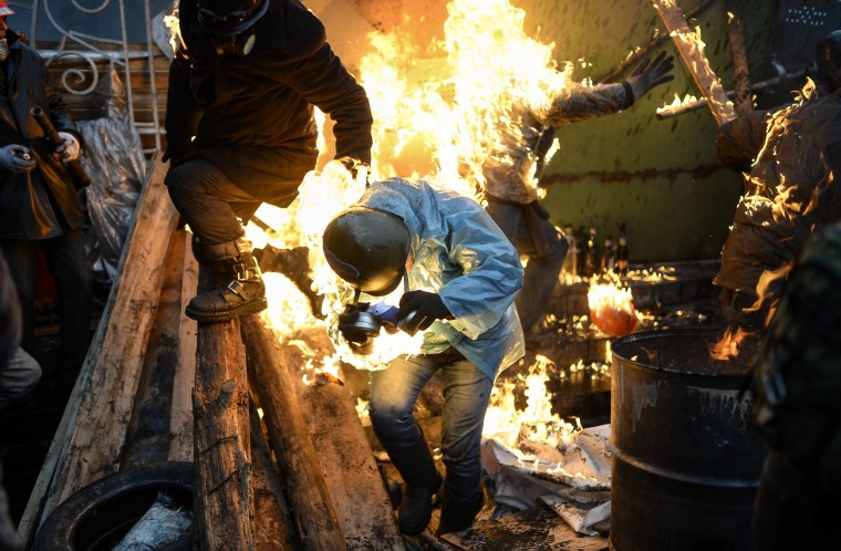 "Protesters catch fire as they stand behind burning barricades during clashes with police on February 20, 2014 in Kiev. Ukraine's embattled leader announced a ""truce"" with the opposition as he prepared to get grilled by visiting EU diplomats over clashes that killed 26 and left the government facing diplomatic isolation. The shocking scale of the violence three months into the crisis brought expressions of grave concern from the West and condemnation of an ""attempted coup"" by the Kremlin. Bulent Kilic/AFP/Getty Images"