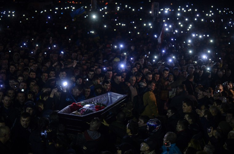 """People carry a coffin of a man who was killed during recent clashes, as they gather at Independence Square on February 22, 2014. Newly freed Ukrainian opposition icon Yulia Tymoshenko received a rapturous welcome on Independence Square on February 22, 2014, declaring """"You are heroes, you are the best of Ukraine"""" to the 50,000-strong crowd before breaking down in tears. The latest developments in the ex-Soviet nation's three-month political crisis came after protesters took control of Kiev's charred city centre and seized Yanukovych's lavish residence on a day of dramatic twists and turns. Bulent Kilic/AFP/Getty Images"""