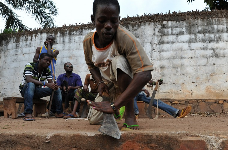 A man sharpens his machete as young people, who created a self-defence committee for their district Benz-vi, meet before leaving for a patrol in their district, on March 12, 2014 in Bangui. UN investigators left for the Central African Republic on March 10 to launch a probe into human right violations in the conflict-ravaged country amid fears of genocide and ethnic cleansing. Sia Kambou/AFP/Getty Images