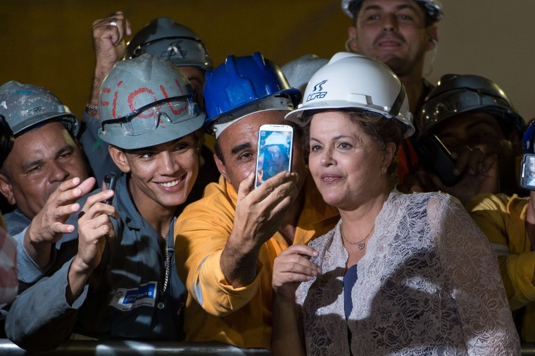 Brazilian President Dilma Rousseff (R) poses with workers during a visit to the construction site of the metro station Sao Conrado (Line 4) in Rio de Janeiro, Brazil, on April 2, 2014. Yasuyoshi Chiba/AFP/Getty Images