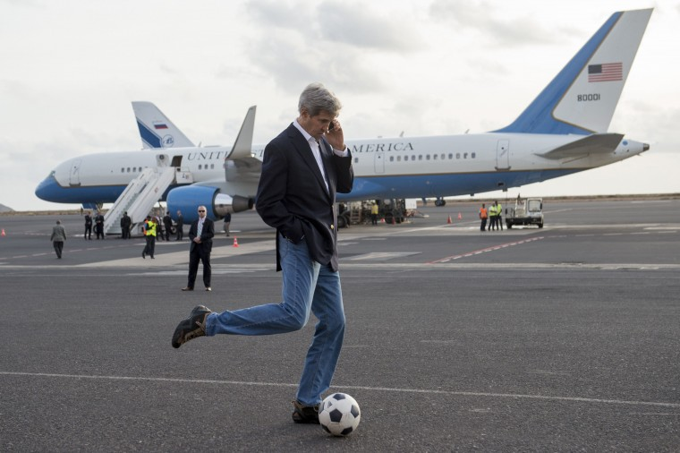 US Secretary of State John Kerry kicks around a soccer ball while talking on his cellphone during an airplane refueling stop at Sal Island, Cape Verde, enroute to Washington, DC, May 5, 2014. SAUL LOEB/AFP/Getty Images