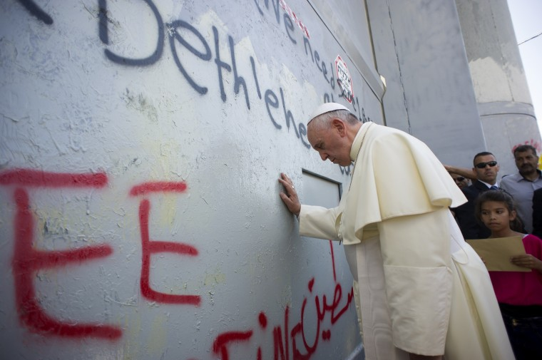 A handout picture released by the Vatican press office shows Pope Francis praying at Israel's separation barrier on May 25, 2014 after he made an unscheduled stop at the security wall drawing attention to the towering eight-metre (26-foot) high concrete wall topped by a guard tower. Pope Francis arrived in Bethlehem to begin the most sensitive part of his three-day Middle East tour aimed at forging regional peace and easing an age-old rift within Handout/AFP/Getty Images