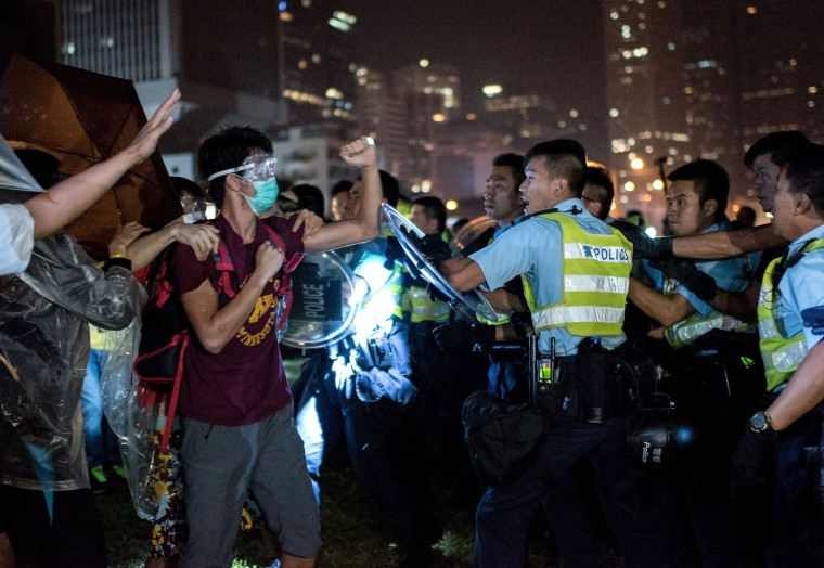 A pro-democracy protester (2L) shakes his fist at police officers as they advance in Hong Kong on October 15, 2014. Hong Kong has been plunged into the worst political crisis since its 1997 handover as pro-democracy activists take over the streets following China's refusal to grant citizens full universal suffrage. ALEX OGLE/AFP/Getty Images