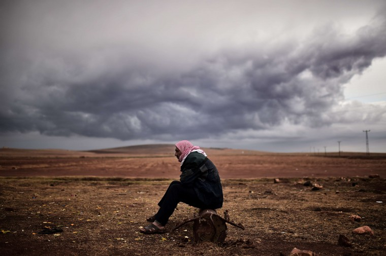A Kurdish man sits at the border area close to the southeastern village of Mursitpinar, in the Sanliurfa province, opposite the Syrian town of Kobane, also known as Ain al-Arab, where heavy fighting between Islamic State militants and Kurdish fighters is taking place, on October 16, 2014. Turkey's ruling party said it was optimistic about the prospects for the peace process with Kurdish rebels after a spate of violence raised concern about its viability. ARIS MESSINIS/AFP/Getty Images