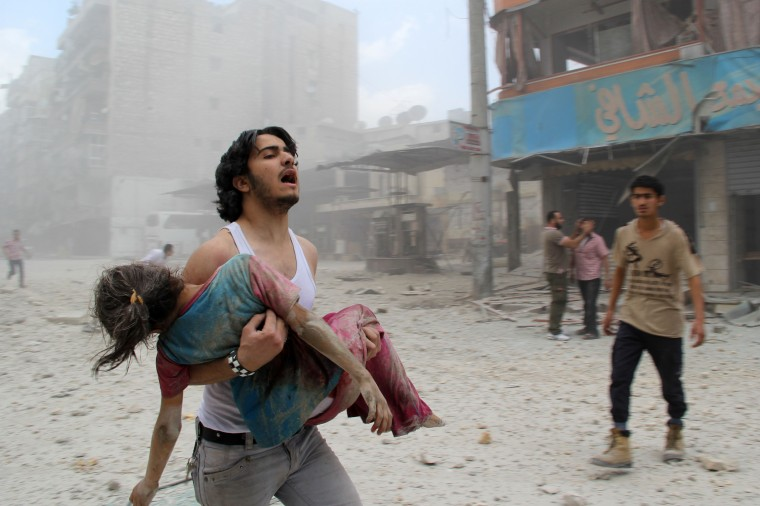 A man carries a young girl who was injured in a reported barrel-bomb attack by government forces on June 3, 2014 in Kallaseh district in the northern city of Aleppo. Some 2,000 civilians, including more than 500 children, have been killed in regime air strikes on rebel-held areas of Aleppo since January, many of them in barrel bomb attacks. BARAA AL-HALABI/AFP/Getty Images