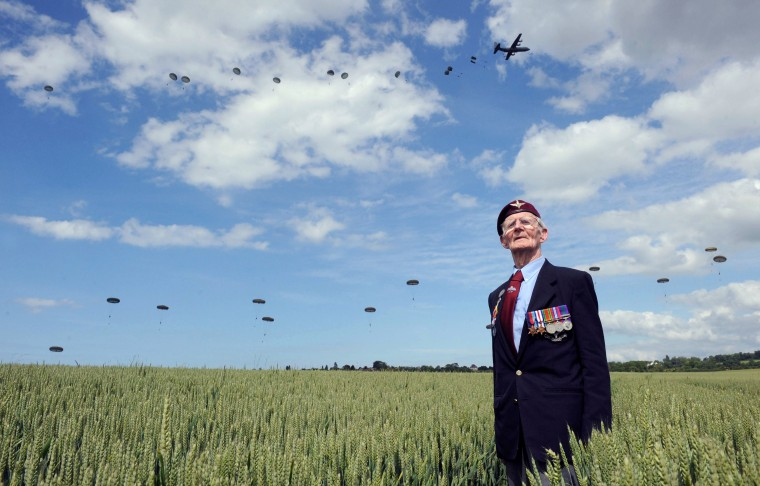 British World War II veteran Frederick Glover poses for a photograph as soldiers parachute down during a D-Day commemoration paratroopers launch event in Ranville, northern France, on June 5, 2014, on the eve of the 70th anniversary of the World War II Allied landings in Normandy. D-Day ceremonies on June 6 this year mark the 70th anniversary of the launch of 'Operation Overlord', a vast military operation by Allied forces in Normandy, which turned the tide of World War II, eventually leading to the liberation of occupied France and the end of the war against Nazi Germany. THOMAS BREGARDIS/AFP/Getty Images