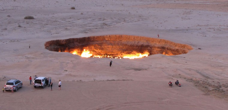 "A picture taken on May 3, 2014, shows people visiting ""The Gateway to Hell,"" a huge burning gas crater in the heart of Turkmenistan's Karakum desert. The fiery pit was the result of a simple miscalculation by Soviet scientists in 1971 after their boring equipment suddenly drilled through into an underground cavern and a deep sinkhole formed. Fearing that the crater would emit poisonous gases, the scientists took the decision to set it alight, thinking that the gas would burn out quickly and this would cause the flames to go out. But the flames have not gone out in more than 40 years, in a potent symbol of the vast gas reserves of Turkmenistan, which are believed to be the fourth largest in the world. IGOR SASIN/AFP/Getty Images"